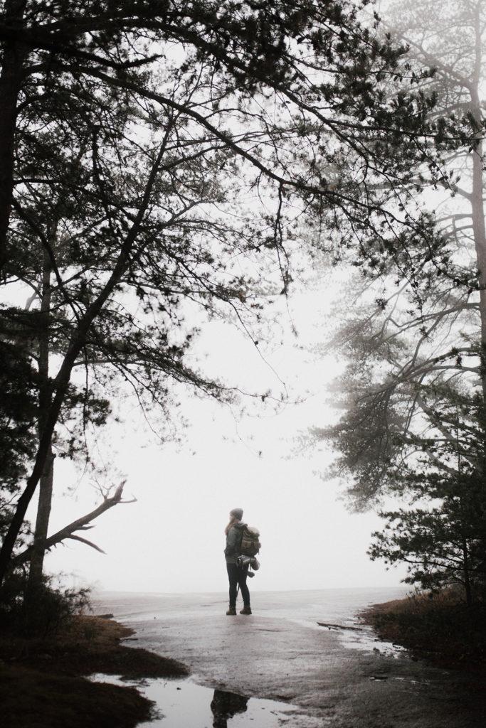 Donna con lo zaino in mezzo alla nebbia
